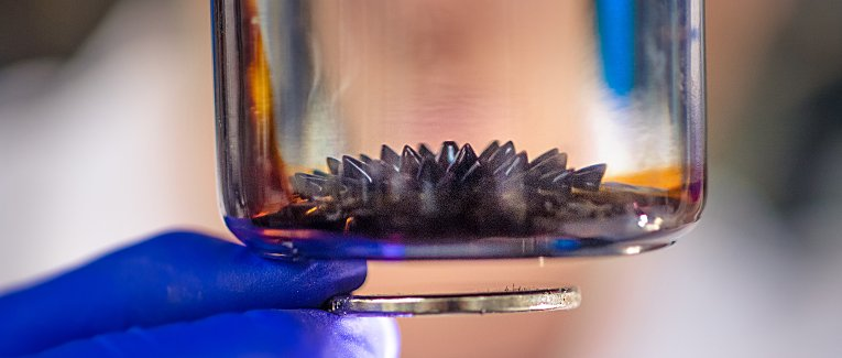 Ferrofluid in a jar with a magnet beneath it.