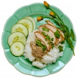 Chicken on a bed of rice with cucumbers and dandelions on the side.