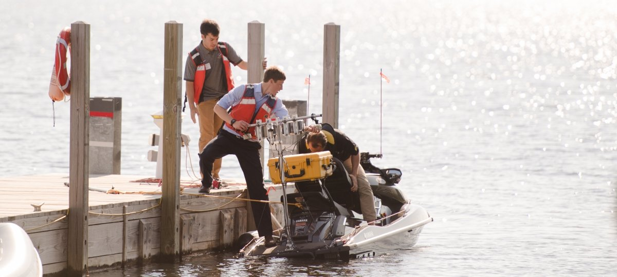 People working on a jet ski at the dock.