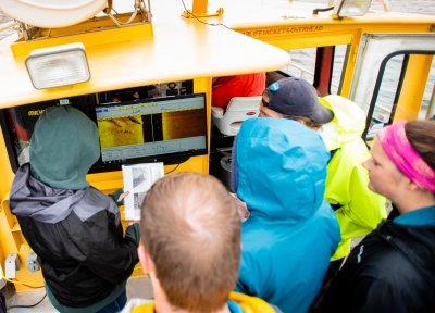 People looking at a sonar screen on a boat.