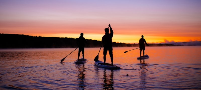 Three people paddleboarding during a sunrise.
