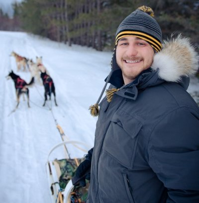 Adam Schmidt on a sled with dogs harnessed up.