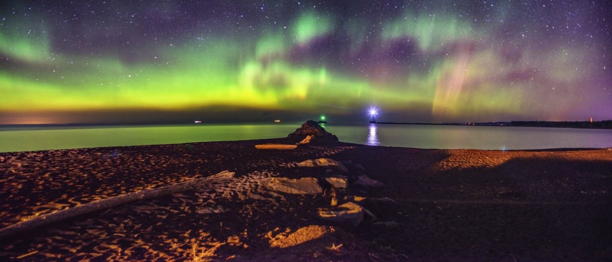 Aurora over the water with a lighthouse in the background.