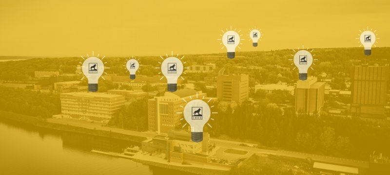 Yellow overlaid photo of campus with lightbulbs on various buildings.