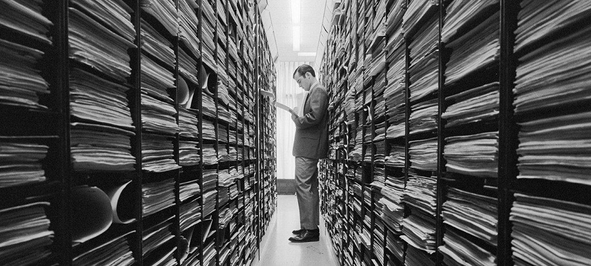 Person standing between shelves of files looking at papers.