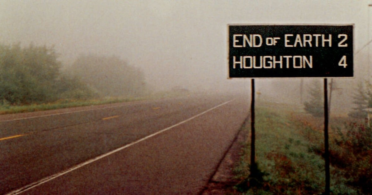 Foggy road with sign showing End of Earth 2 miles, Houghton 4 miles.