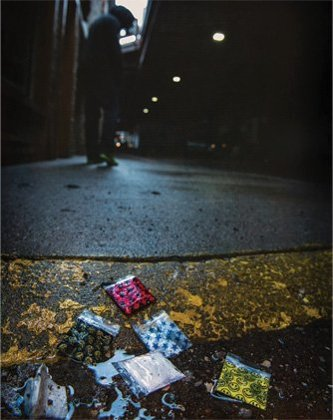 Colorful baggies filled with unknown substances sitting on a wet curb