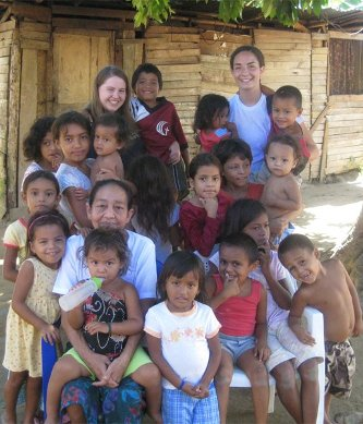 Ashley (Thode) Julien '10, left, and Esther Johnson '09 standing behind Honduran children and a woman from the community where they had hoped to build a school. <em>Photo: Ashley Maes</em>