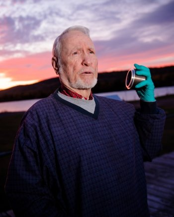 A man with short white hair and trimmed beard holds a piece of metal equipment in his gloved hand with a sunrise behind him