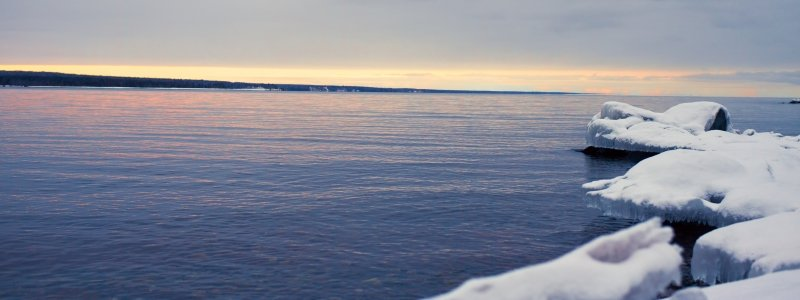 Ice-covered rocks extend out into Keweenaw Bay at sunset.
