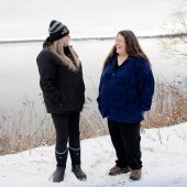 Two laughing women stand next to an icy Keweenaw Bay