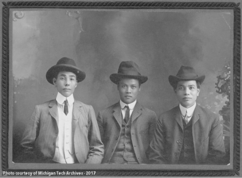 Three men in suits, ties, and fedora hats pose in a black and white archival photo against a plain dark gray background.