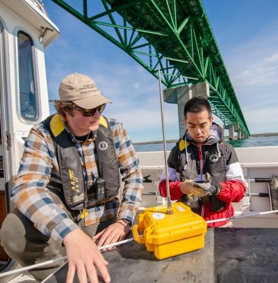 Two people on a boat under the Mackinac Bridge setting up equipment.