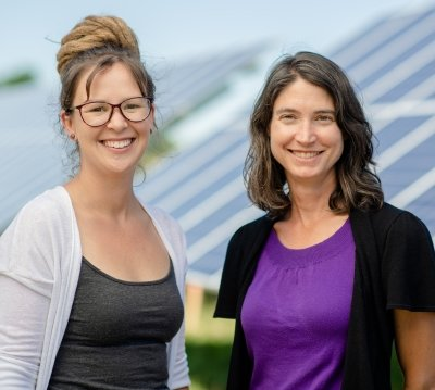 Chelsea Schelly and Richelle Winkler standing in front of a row of solar panels.