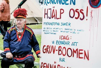 A Sámi man displays a placard appealing to the Swedish king to help in the battle against mining on Sámi land.