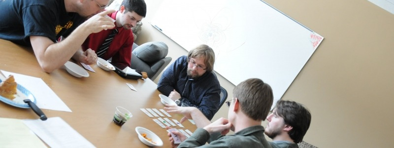 Graduate students discussing card strategy around a table