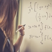 Woman writing out math equations on a whiteboard.