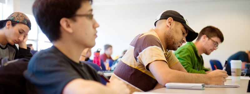 Student taking notes in Mathematics course