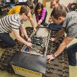 Students work together kneeling on a large piece of equipment