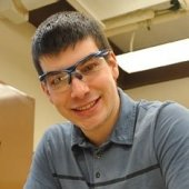 student smiling with safety glasses on