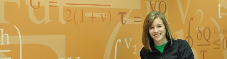 Student smiling with a wall filled with equations