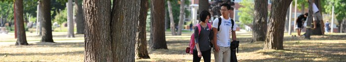 A young couple walking between trees on campus