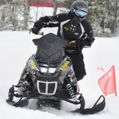 Someone on a snowmobile going around a track marked with a small flag