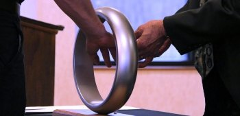 An engineer places their hand through a steel ring to receive the Order of the Engineer.
