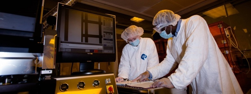 Two researchers in full protective gear look over notes in a binder inside the Microfabrication lab