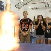 Mind Trekkers students watching fire from a large bottle.