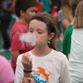 Mind Trekkers student exhaling what looks like smoke as a part of an experiment.