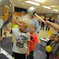 Students hair sticking up while touching a Van de Graaff generator.