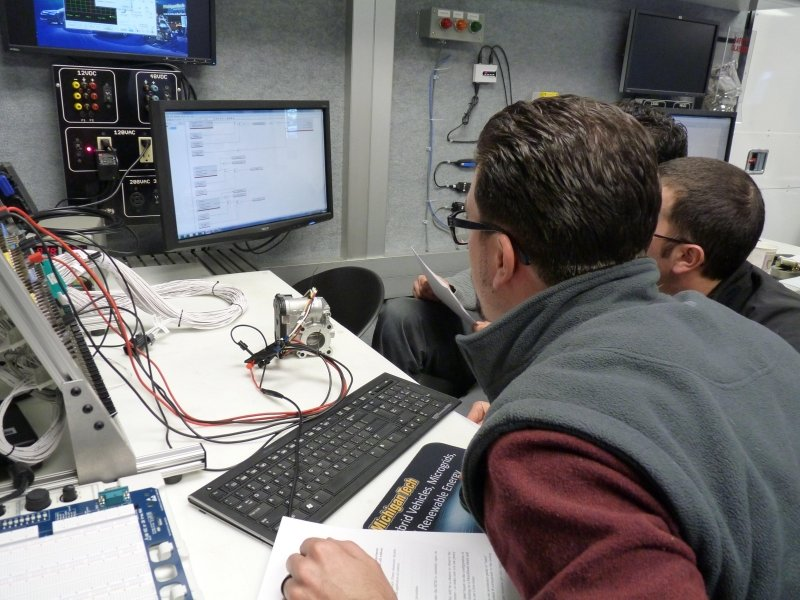 Participants work inside the Mobile Lab while looking at monitors.