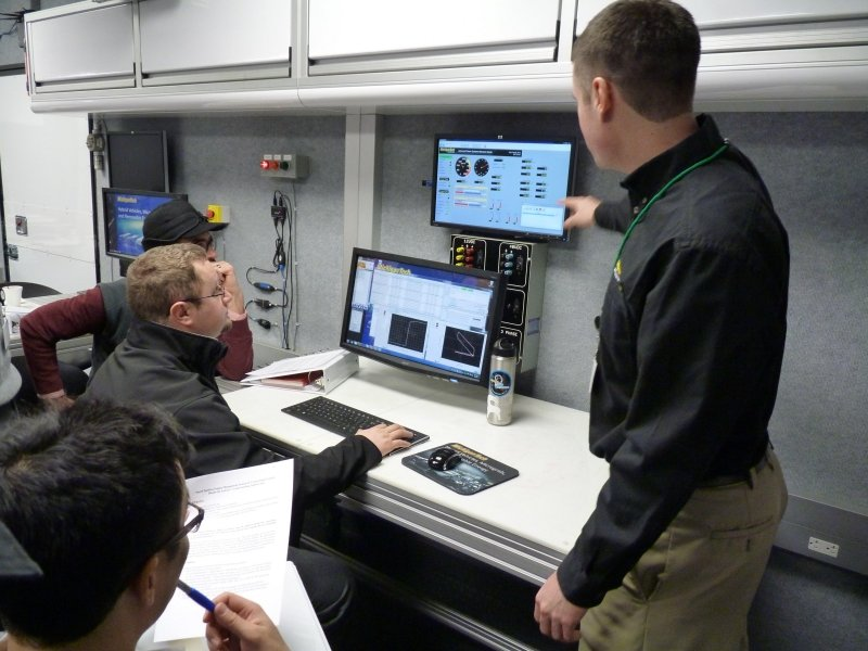 A lecturer pointing at a monitor while three participants look on.