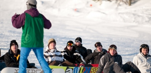 Instructor teaching a snowboarding PE class.