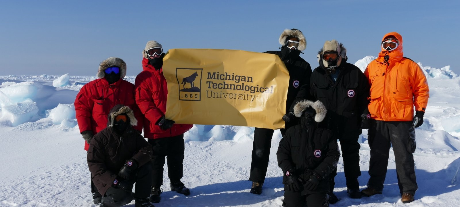 MTRI Scientists working on an arctic sensing project and holding a Michigan Tech banner near Barrow, AK
