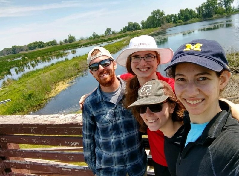 Four interns on a deck with wetlands in the background.
