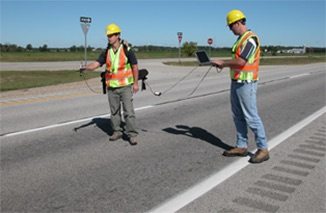 Two people using equipment on a road.
