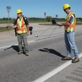 Two people taking measurements on a road.