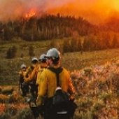 Firefighters in front of a wildfire.