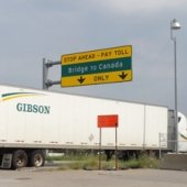 Semi truck driving under Bridge to Canada sign.