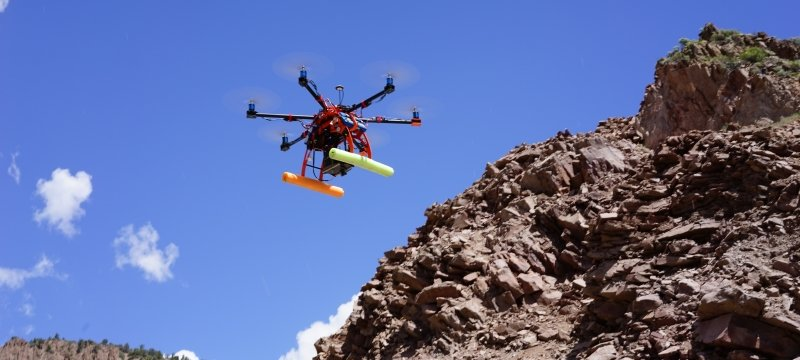 Hexacopter flying above a rocky hill.