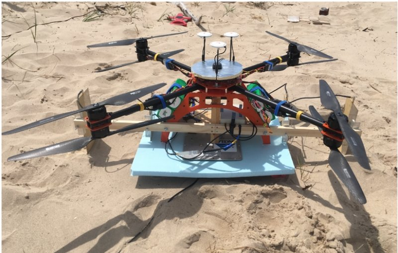 Quadcopter on a board on the sand.
