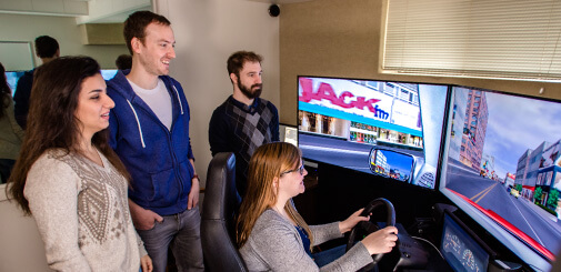 Three students watching another studnet test a driving simulator.