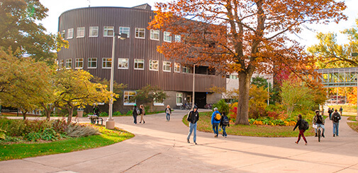 Students walking accross Michigan Tech Campus on an autumn day