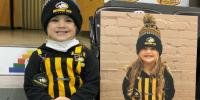 A little group with a Michigan Tech Huskies hat and black and gold striped overalls       sits with her fan cutout sign with her Michigan Tech hat on.