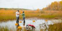 Two people in high boots stand in a wetland gathering a water sample.