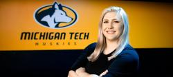 Kaitlyn Roose stands in front of the Michigan Tech Huskies logo.