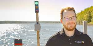 Tech alum Jake Soter runs the SwimSmart Warning System through its paces on the docks       of Michigan Tech's Great Lakes Research Center.