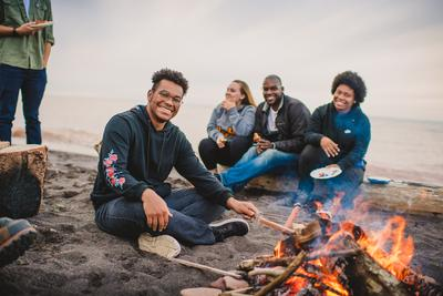 Students at a bonfire on the beach.
